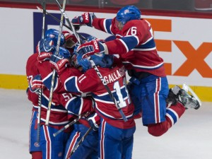 Montreal Canadiens' P.K. Subban leaps onto teammates celebrating a goal by Francis Bouillon to beat the Ottawa Senators 5-4 during overtime period NHL hockey action Saturday, March 15, 2014 in Montreal. THE CANADIAN PRESS/Paul Chiasson